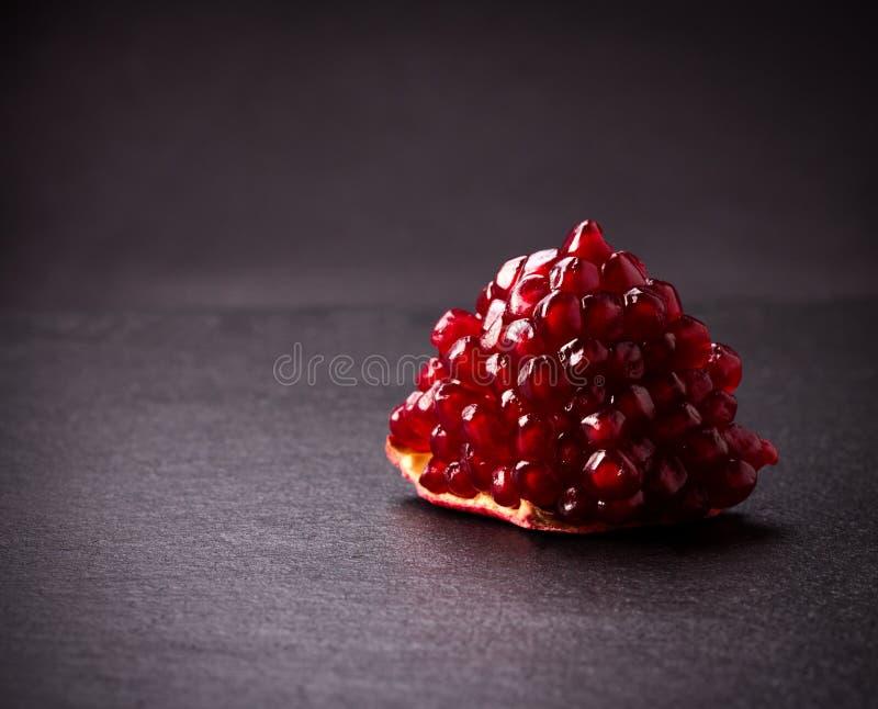 Some red pomegranates on black slate plate. Some red juicy pomegranate, whole and broken, on black slate plate stock image