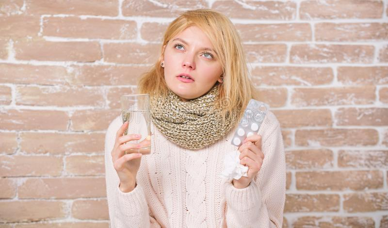 Some relief from cold. Ill woman treating symptoms caused by cold or flu. Unhealthy woman holding pills and water glass. Cute sick girl taking anti cold pills royalty free stock images
