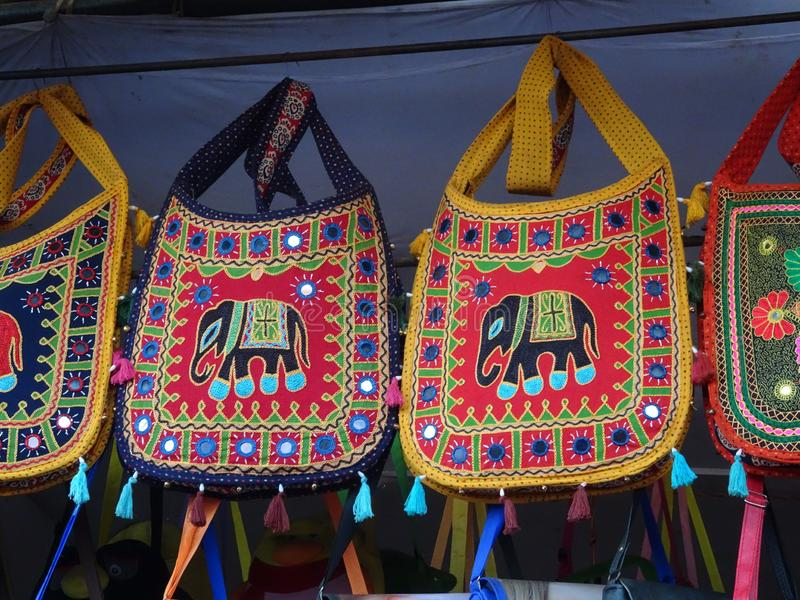 Some stylish beautiful cotton blend shoulder bags with elephant embroidery mirrorwork hanged from ceiling royalty free stock photography