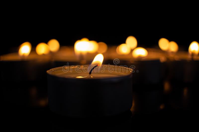 Some tealights in the dark. Many burning candles with shallow depth of field - peace concept royalty free stock photo