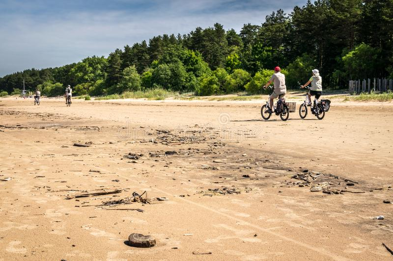 Some tourists on bicycles on a beach royalty free stock image