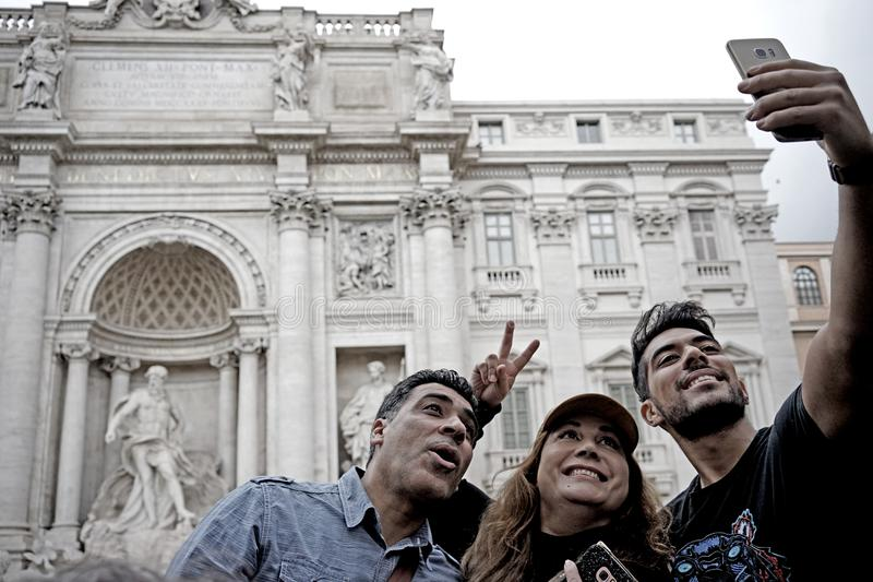 Some tourists take a picture in Trevi Fountain in Rome royalty free stock images