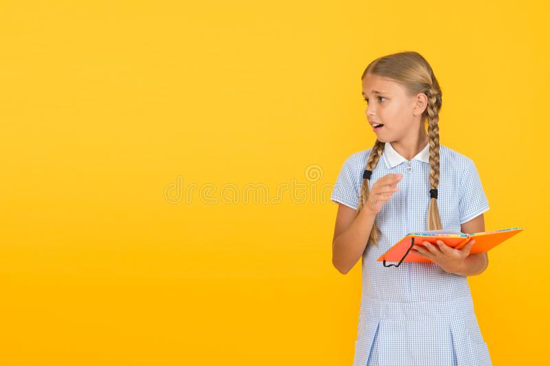 Some troubles. Cute small child reading book on yellow background. Adorable little girl learn reading copy space. Home. Reading and schooling. Study hard. Exam royalty free stock photography