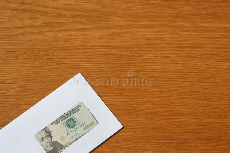 Some US dollars banknotes in the white black envelope for a bribe in the office at the table. Bribe of some US dollars banknotes in the blank white envelope over royalty free stock photography