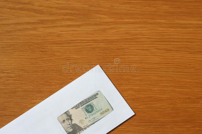 Some US dollars banknotes in the white black envelope for a bribe in the office at the table. Bribe of some US dollars banknotes in the blank white envelope over royalty free stock images