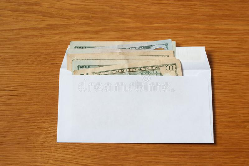Some US dollars banknotes in the white black envelope for a bribe in the office on the table. Bribe of some US dollars banknotes in the blank white envelope over stock photography