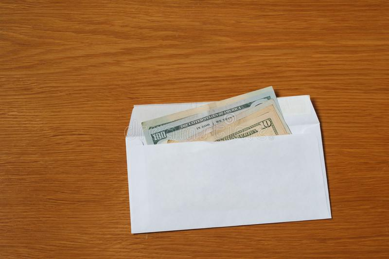 Some US dollars banknotes in the white black envelope for a bribe in the office at the table. Bribe of some US dollars banknotes in the blank white envelope over stock photography