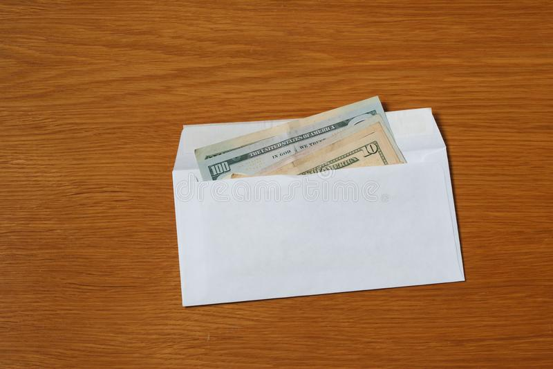 Some US dollars banknotes in the white black envelope for a bribe in the office at the table. Bribe of some US dollars banknotes in the blank white envelope over stock images