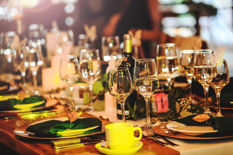 Some wine glasses, plates, forks and green briefcases for event celebration. Beautiful dinner table setting. Vintage decoration of. Reception table. Elegant stock image