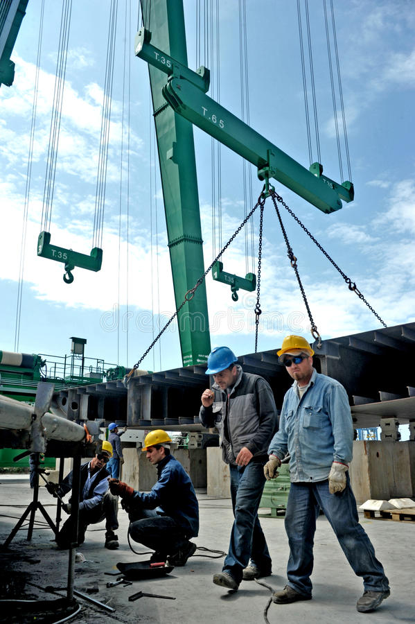 Some workers working at a shipyard between big cranes for the construction of a mega yacht royalty free stock images