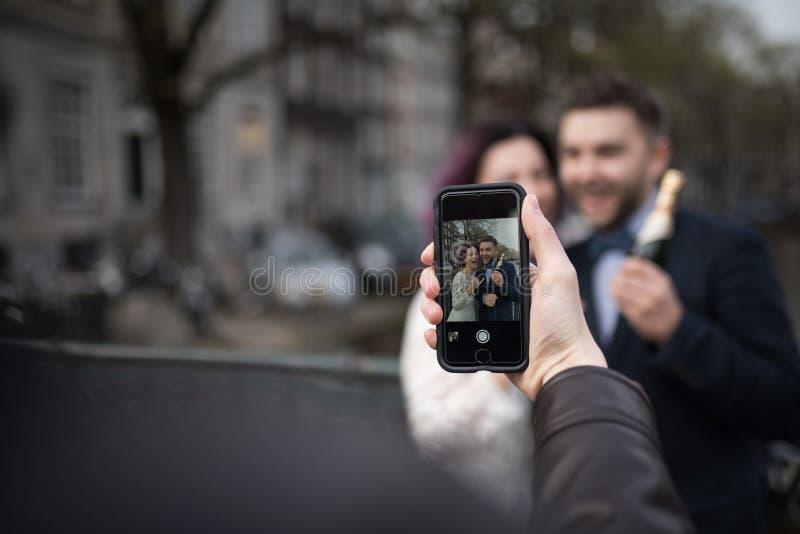 Somebody gebruikt smartphone om een foto van jonggehuwden in de stad te maken royalty-vrije stock afbeeldingen