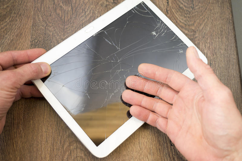 Somebody holds tablet PC with broken touchscreen stock images