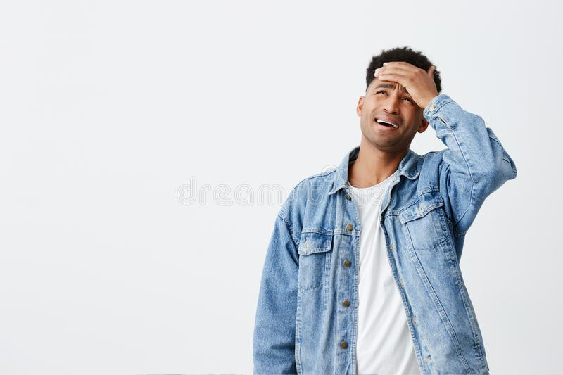 Somebody please do it instead of me. Portrait of unhappy tan-skinned man with dark curly hair in white t-shirt and blue. Jacket holding hand on forehead, going stock photos