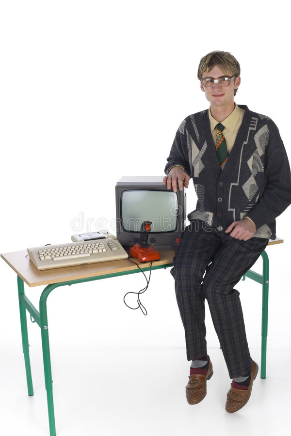Someday I'll be rich... Nerdy man sitting on table next to old-fashioned computer. Smiling and looking at camera. Front view, white background. Whole body royalty free stock image