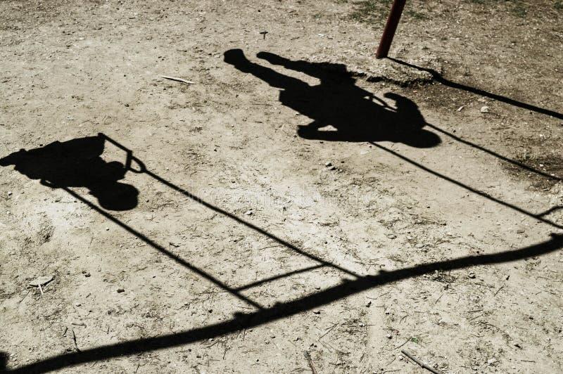 Somente a sombra de duas crianças é crianças visíveis monta em um balanço foto de stock