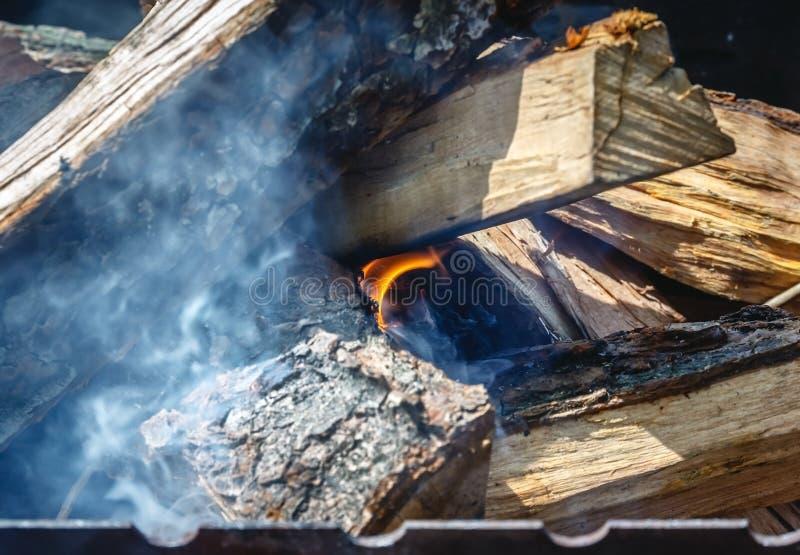 Somente tomou apareceu o fogo entre o madeira-fogo na grade imagens de stock royalty free