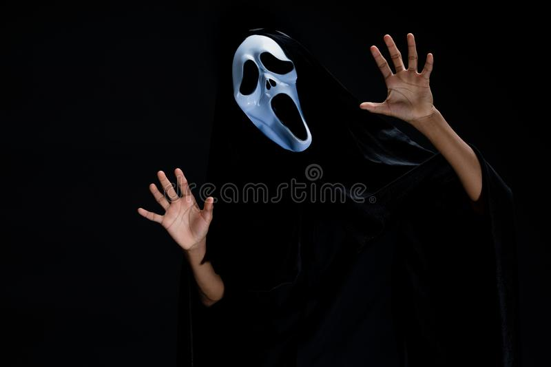 Someone in black cover with white ghost mask cosplay to devil ac royalty free stock image