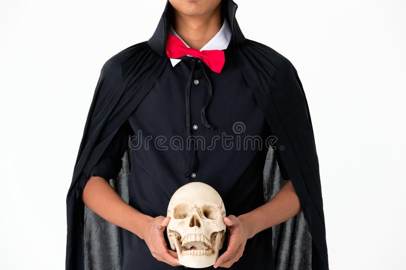 Someone in black dress look like witch holding skull on white ba royalty free stock photography