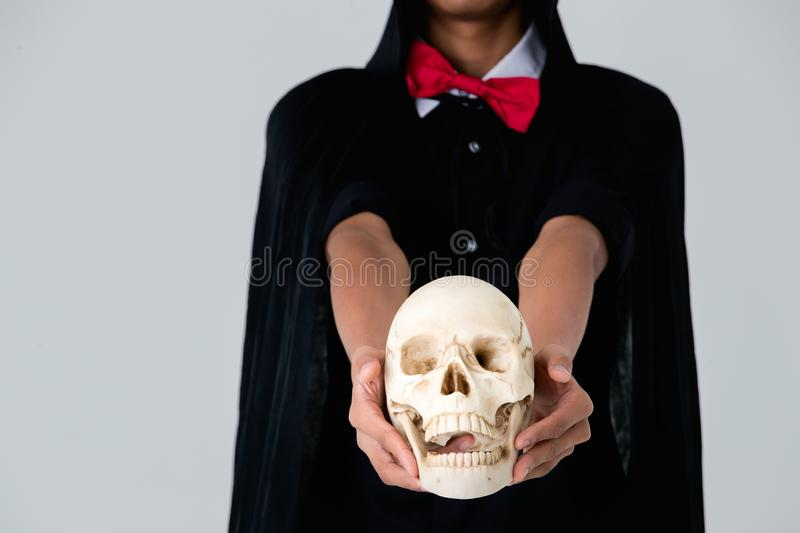 Someone in black dress look like witch holding skull on white ba royalty free stock photos