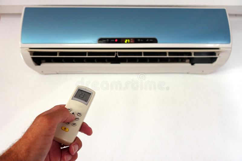 Someone changing the settings of a domestic AC or Air Conditioning unit with a remote control - focus on the remote - copy space. For text royalty free stock images