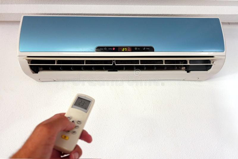 Someone changing the settings of a domestic AC or Air Conditioning unit with a remote control - focus on the wall unit - copy spa. Ce for text stock photo
