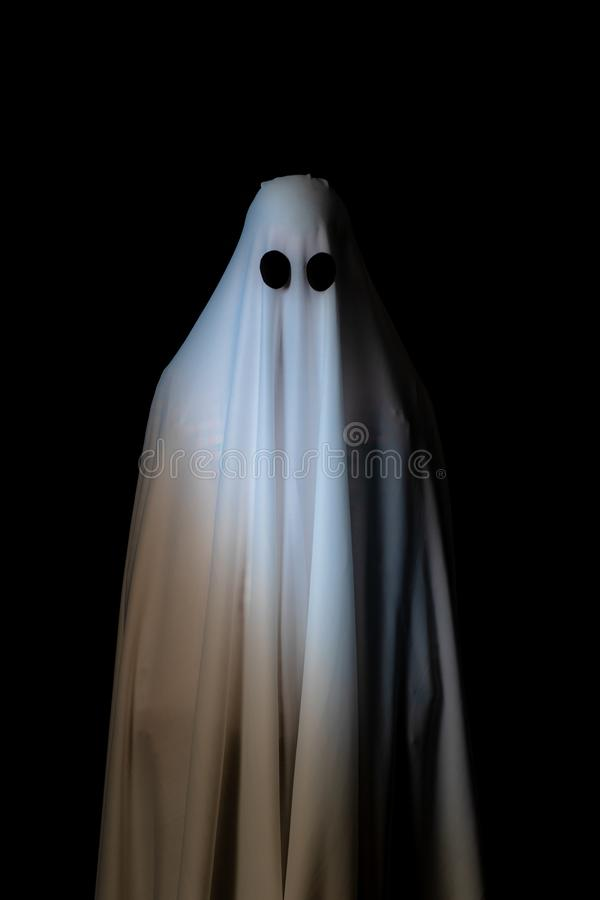 Someone covered with white cloth with big black eyes on black ba stock photos