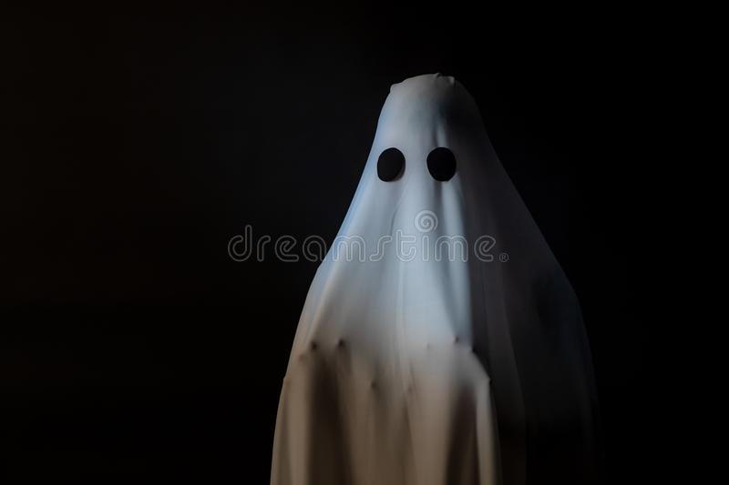Someone covered with white cloth with big black eyes on black ba stock photo