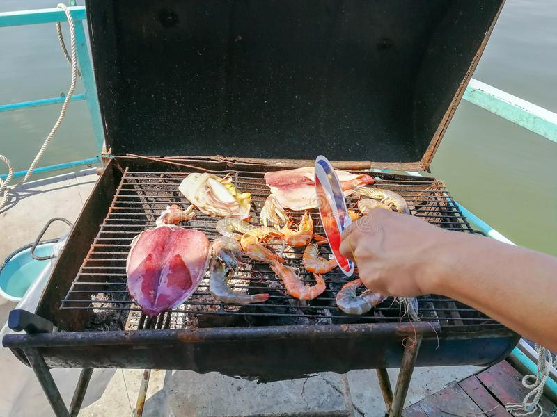 Someone hand winding and grilling seafood, prawn, and squid on t stock image