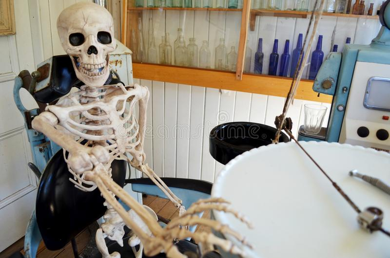 Someone having dental work. Old vintage dentistry equipment photograph with skeleton concept afraid scared hesitant or cuts to healthcare budgets and high stock photo