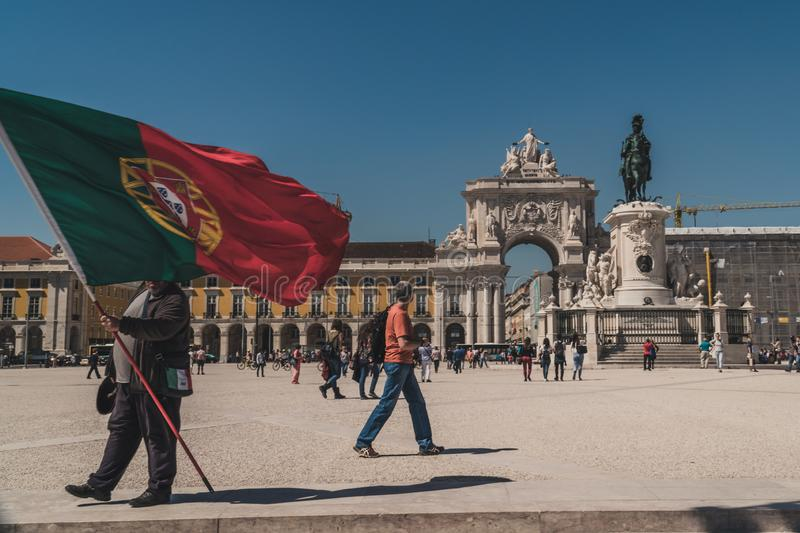 Someone holds a giant flag of Portugal on the Praça do Comércio Commerce Square in downtown Lisbon. The square is busy, with many tourists walking. In royalty free stock photo