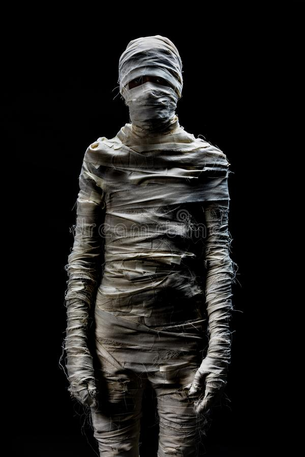 Someone in peices of cloths as mummy cosplay on black background royalty free stock photography