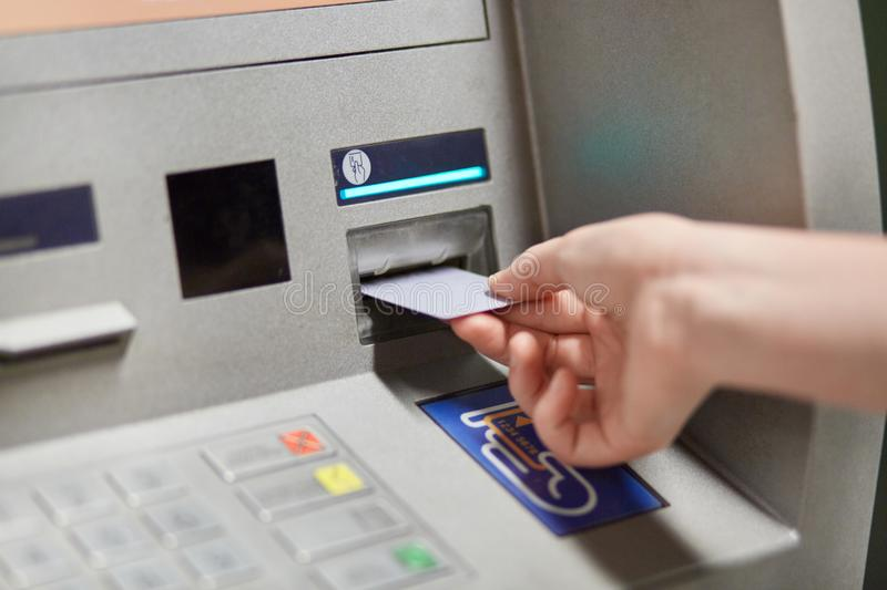 Someone takes off money from outdoor bank terminal, inserts plastic credit card in atm machine, going to withdraw money and get sa stock photo