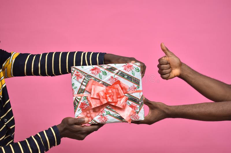 someone taking presents from another person, giving thumbs up royalty free stock photography