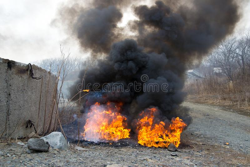 Something,for example, a car caught fire in spring. Arson due to riot or revolution or terrorism in early spring or fall. Smoke stock images