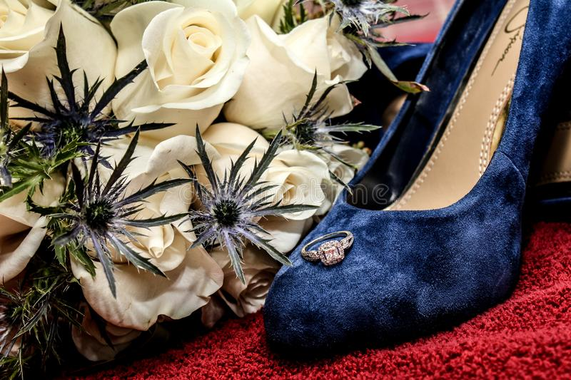 Bride`s Engagement Ring Resting on her Blue Suede Wedding Shoes stock images