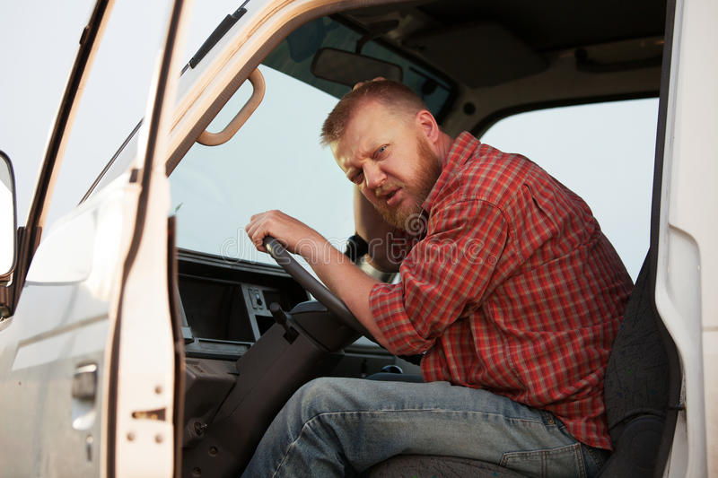 Somewhat puzzled bearded driver in the cab royalty free stock photography