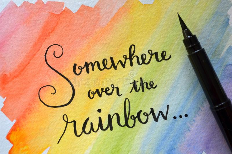 SOMEWHERE OVER THE RAINBOW hand-lettered in notebook. On rainbow-colored background vector illustration