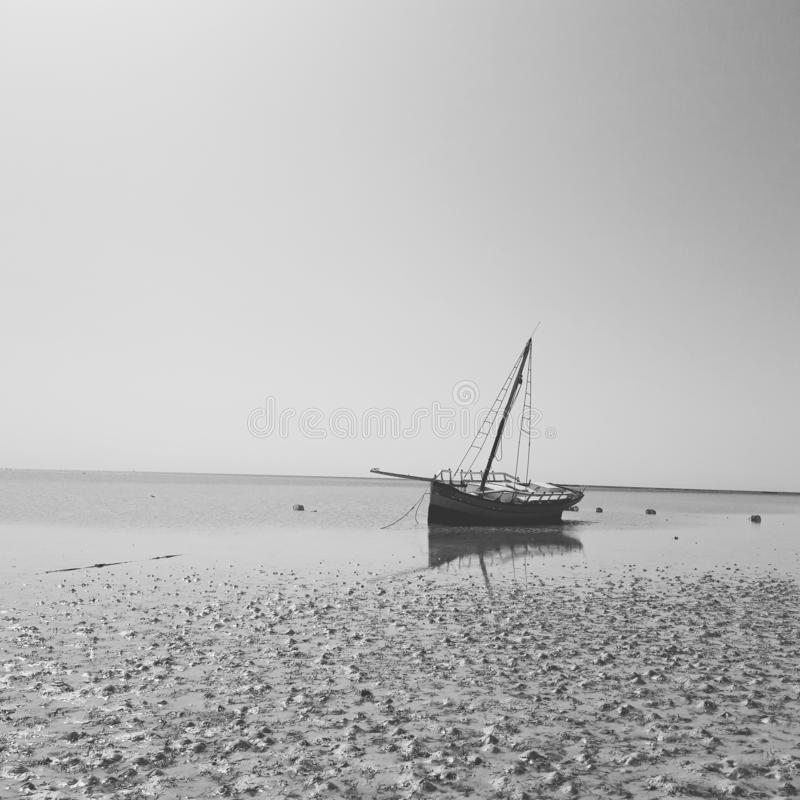 Somewhere in Tunisia a boat on a beach black and white pic royalty free stock images