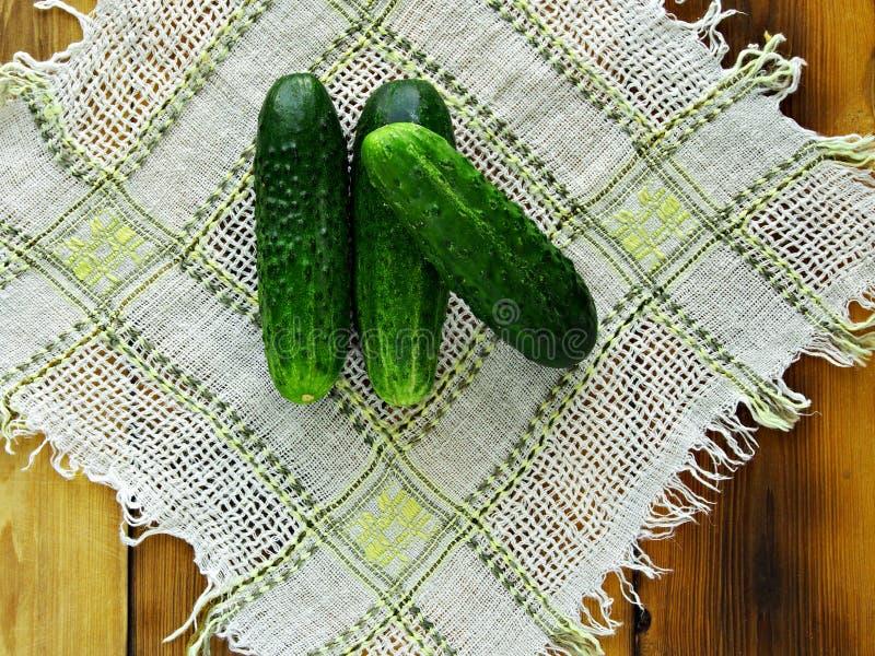 Sommar är tiden av plockninggrönsaker och frukter Nya gurkor komponeras av en liten glidbana på en silkespapperservett, på en fli royaltyfria foton