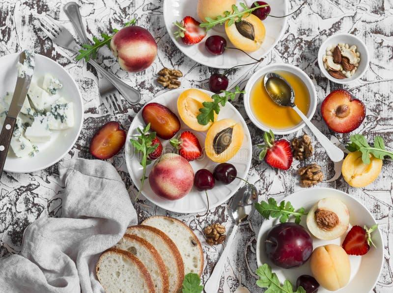 Sommar bär frukt - aprikors, persikor, plommoner, körsbär, jordgubbar och ädelost, honung, valnötter på en ljus stenbakgrund läka arkivbilder