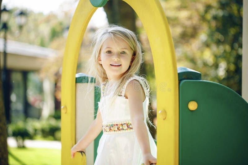 Sommar-, barndom-, fritid-, gest- och folkbegrepp - lycklig liten flicka som spelar på barnlekplats arkivbilder