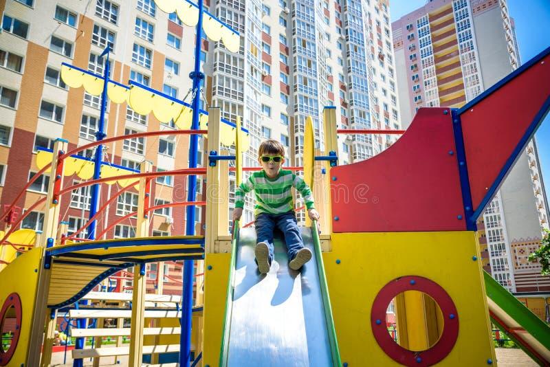 Sommar, barndom, fritid, kamratskap och folkbegrepp - den lyckliga pysen p? barnlekplats gled fr?n kullen royaltyfria bilder