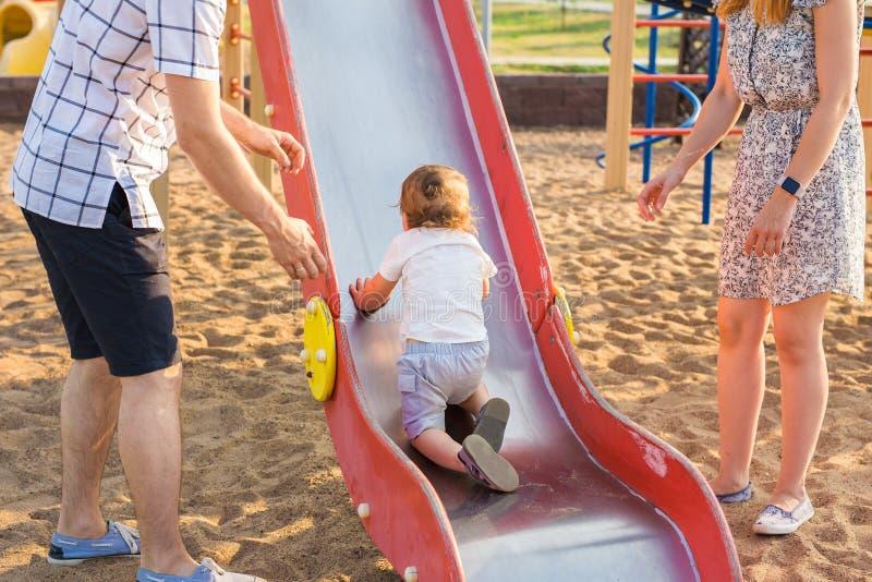 Sommar, barndom, fritid och familjbegrepp - lyckligt barn och hans föräldrar på ram för barnlekplatsklättring arkivfoto