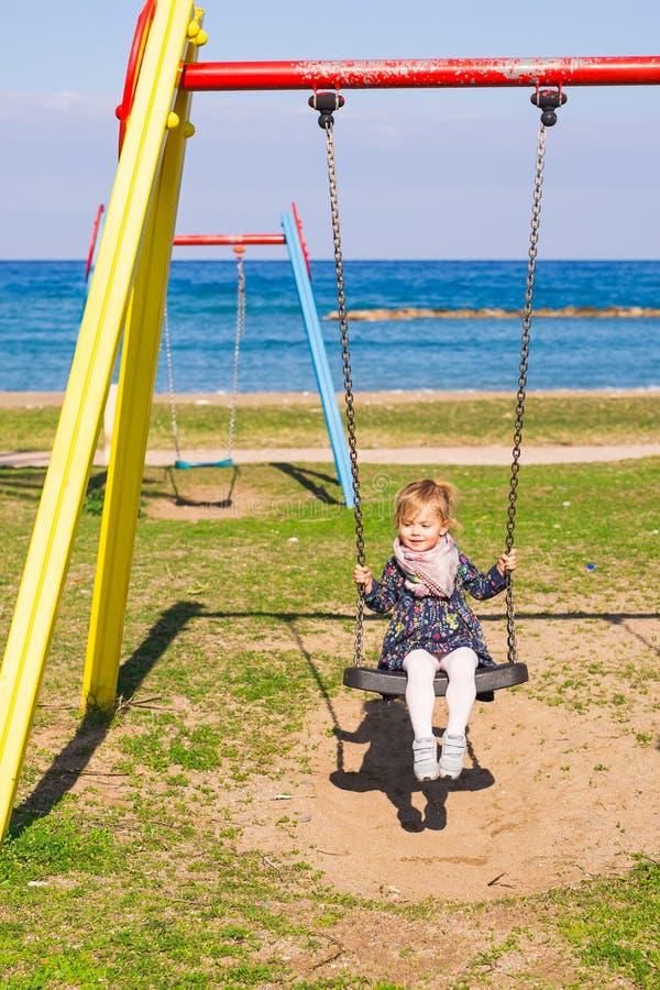 Sommar, barndom, fritid och folkbegrepp - lycklig liten flicka på barnlekplats arkivbilder