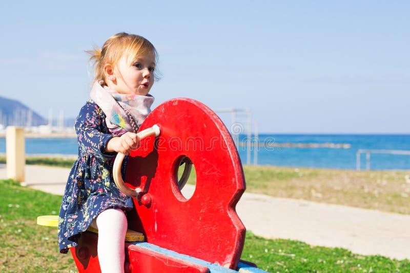 Sommar, barndom, fritid och folkbegrepp - lycklig liten flicka på barnlekplats fotografering för bildbyråer