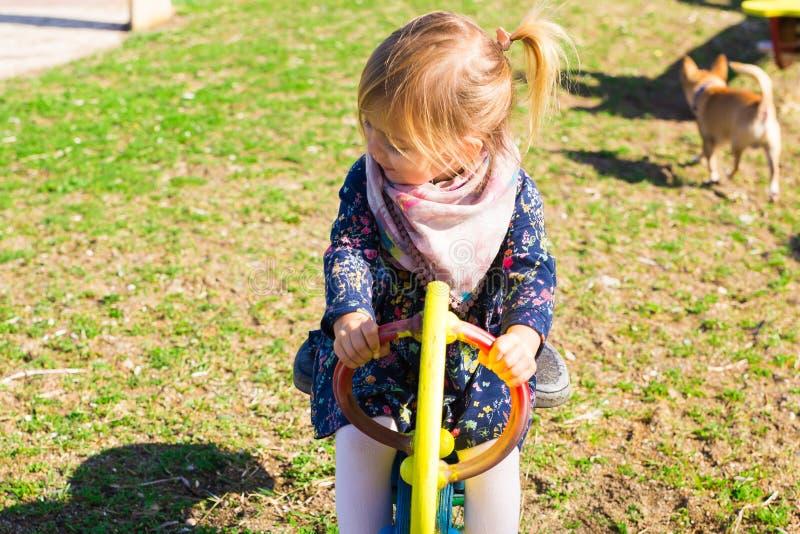 Sommar, barndom, fritid och folkbegrepp - lycklig liten flicka på barnlekplats royaltyfria foton