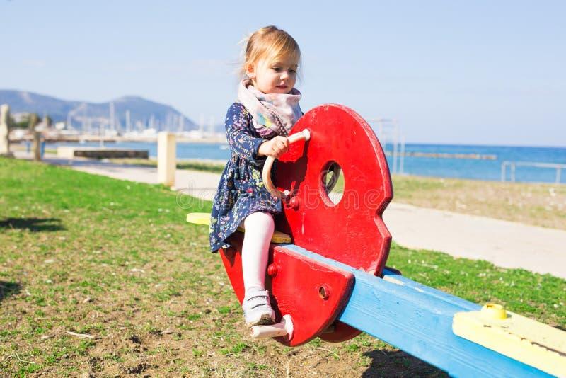 Sommar, barndom, fritid och folkbegrepp - lycklig liten flicka på barnlekplats arkivfoto