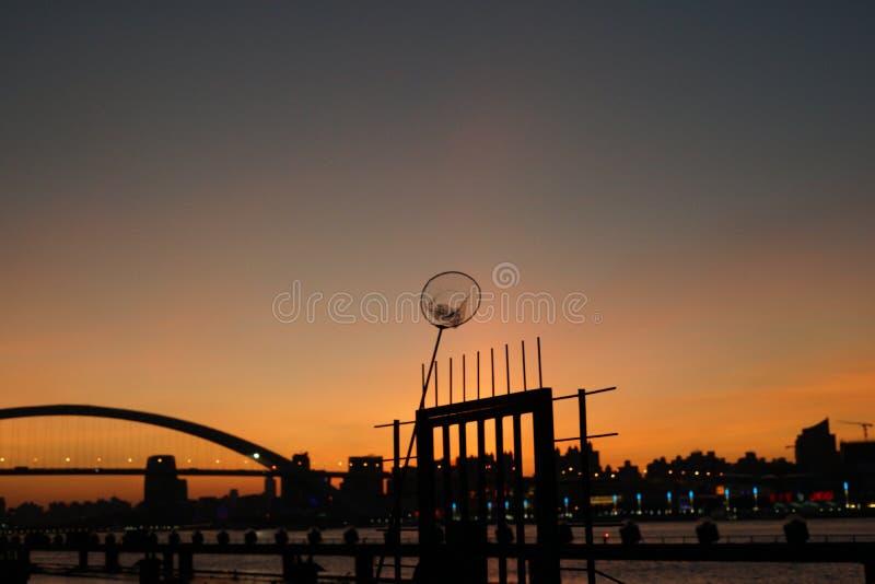 Sommar för bro för stadssolnedgångflod arkivbild
