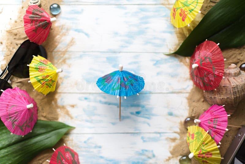 sommar för snäckskal för sand för bakgrundsbegreppsram Strandparaplyer på en träblå bakgrund arkivfoton