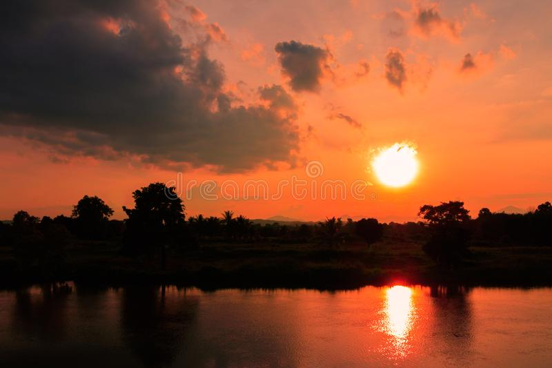 Sommar för tid för skymning för natur för afton för blå himmel för landskap för solnedgång färgrik och träd för kontur för flodre arkivbild
